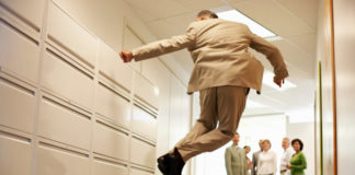 Senior Businessman Jumping in Corridor